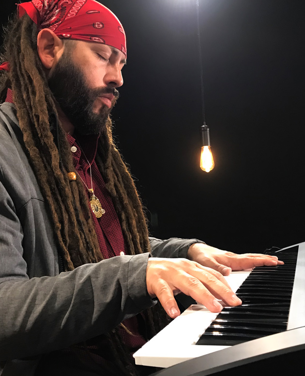 man with dreadlocks playing keyboard
