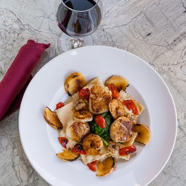 shrimp pasta dish and glass of red wine
