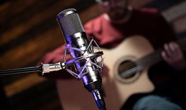 microphone with man holding acoustic guitar in background