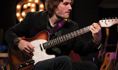 man playing Michael Kelly electric guitar