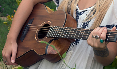 woman holding small brown acoustic guitar