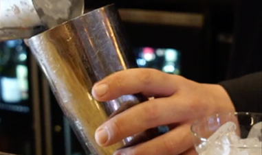 closeup of man's hands making iced drink