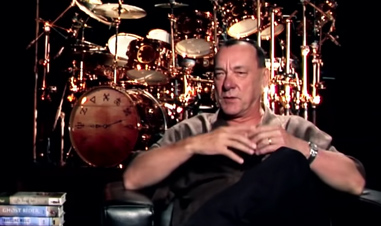 man in front of large drum set