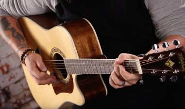 partial view of man playing acoustic guitar