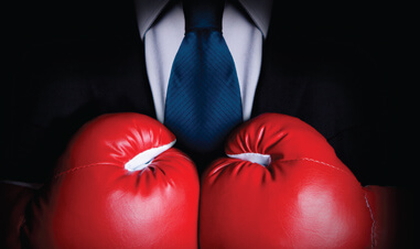 partial view of businessman wearing boxing gloves